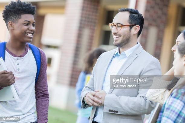 Hispanic male teacher visits with students before class