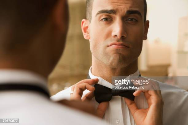 Hispanic man adjusting bowtie