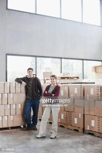 Hispanic man and woman in warehouse