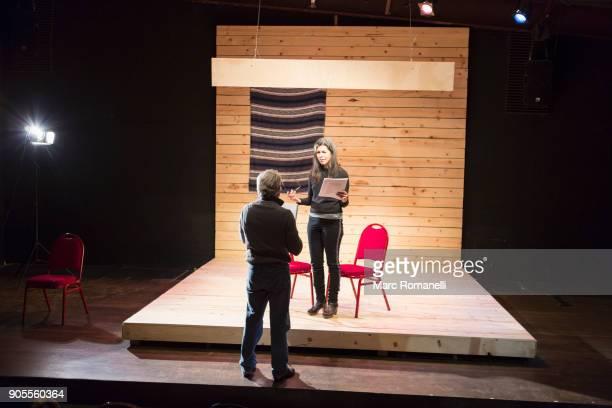 hispanic man and woman reading scripts on theater stage - actriz fotografías e imágenes de stock