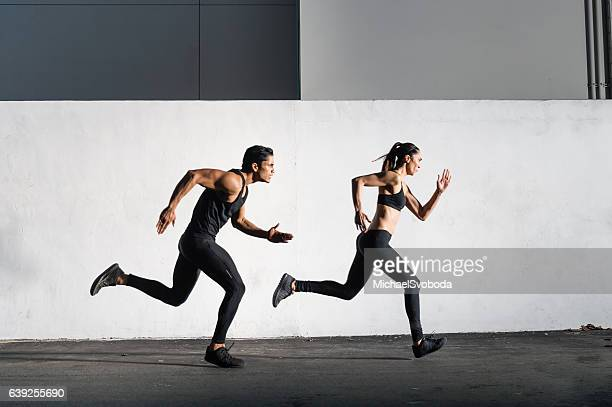 hispanic man and women running together - running stock pictures, royalty-free photos & images