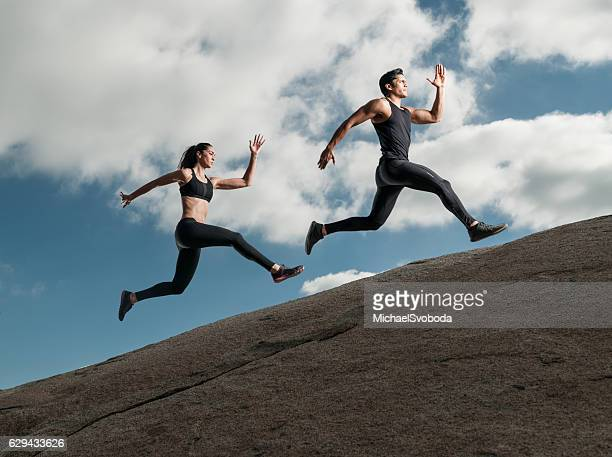 Hispanic Man and Women Running Up A Granite Boulder