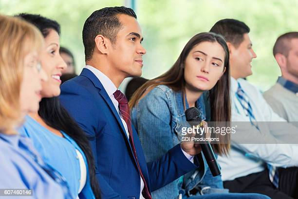 hispanic man asks question during meeting - town hall meeting stock photos and pictures