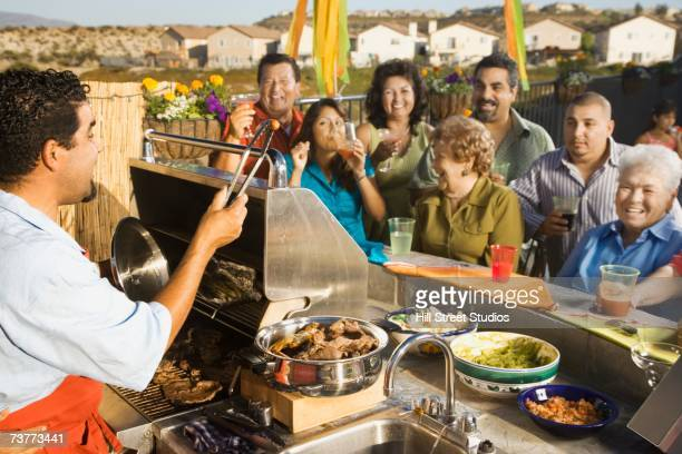 Hispanic man barbecuing for large family on patio