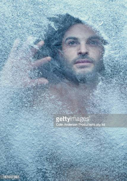Hispanic man behind snow covered window