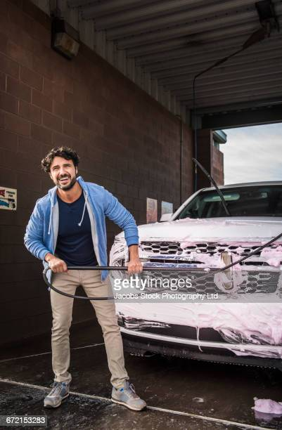 hispanic man brushing car at self-serve car wash - car wash brush stock photos and pictures