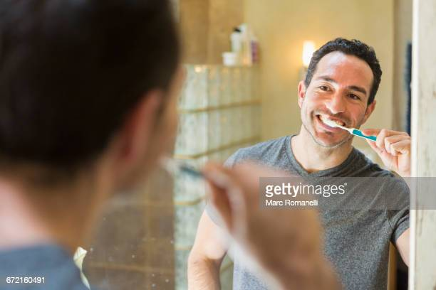 Hispanic man brushing teeth in mirror