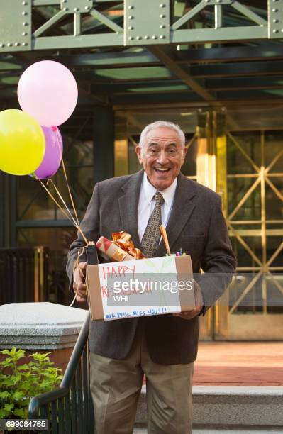Hispanic man carrying belongings with happy retirement sign and balloons