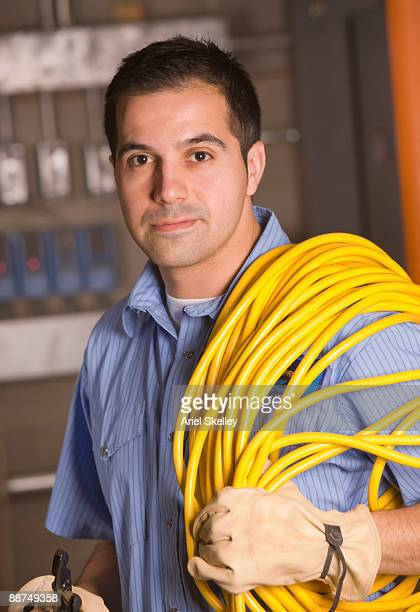 Hispanic man carrying electrical cord