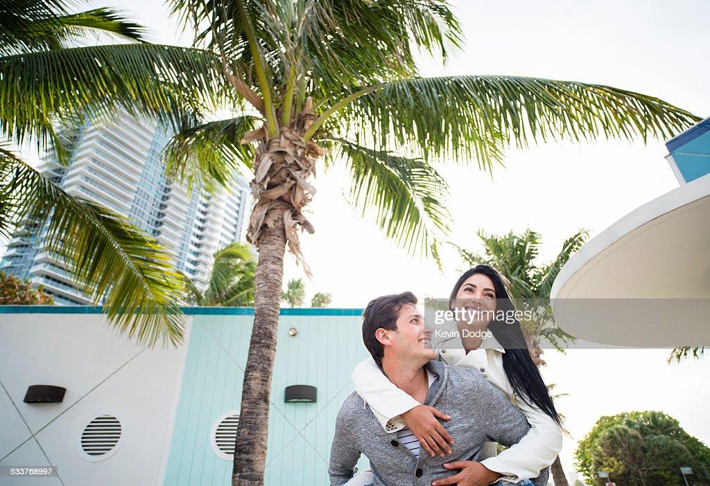 Hispanic man carrying girlfriend piggyback outdoors : Foto stock