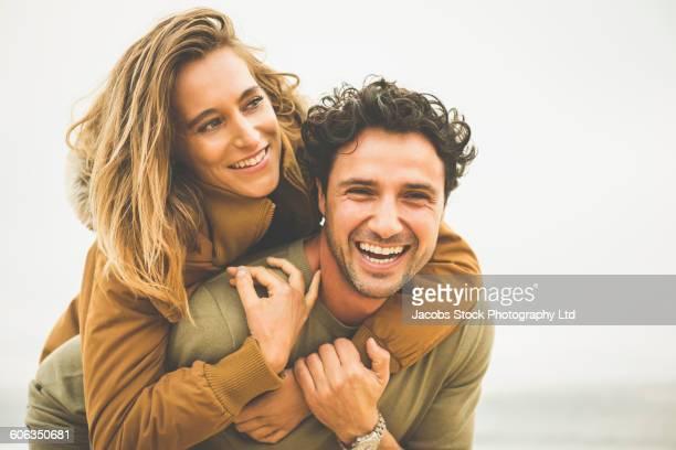 Hispanic man carrying girlfriend piggyback outdoors
