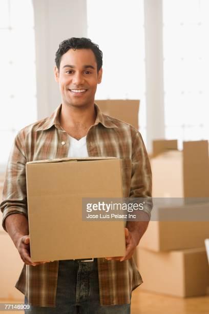 Hispanic man carrying moving box