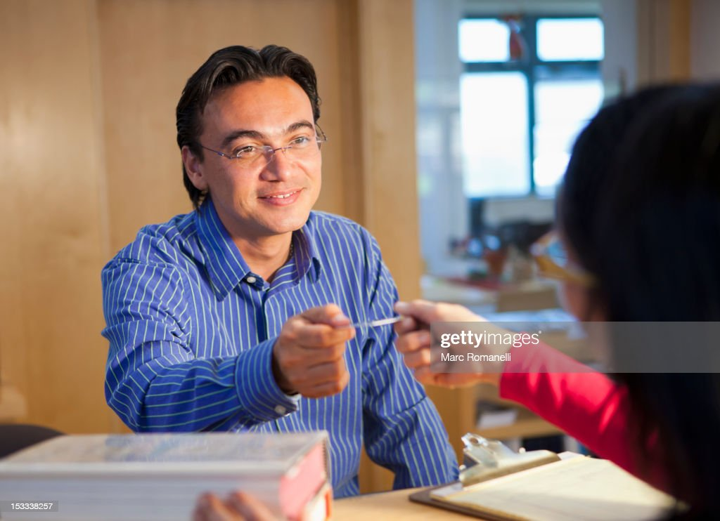 Hispanic man checking out books with library card : Stock Photo