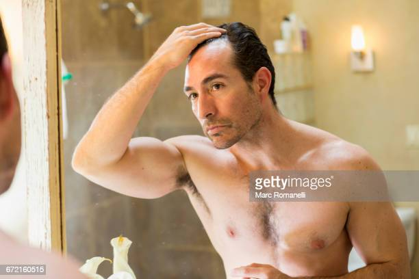 Hispanic man checking receding hairline in mirror