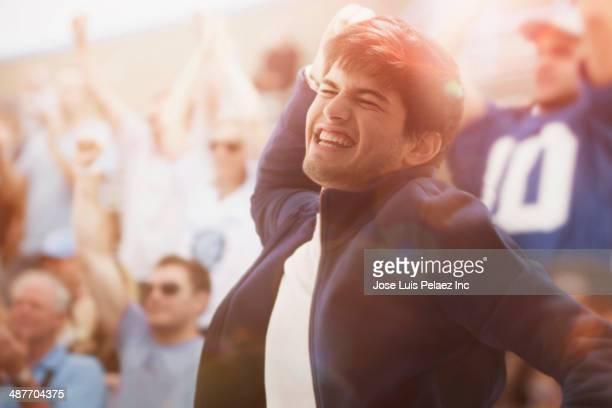 Hispanic man cheering at sporting event