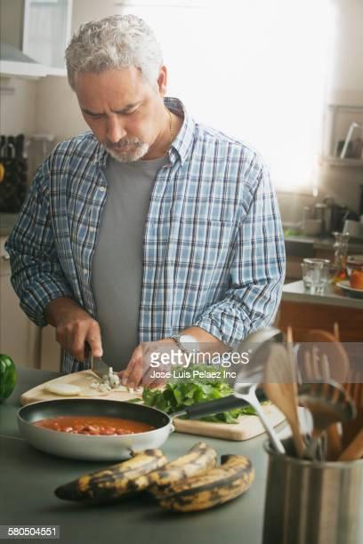 Hispanic man cooking in kitchen