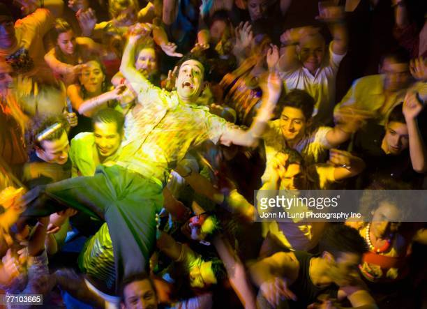 Hispanic man crowd surfing at nightclub