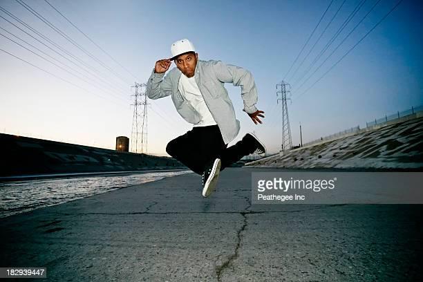 Hispanic man dancing on urban street