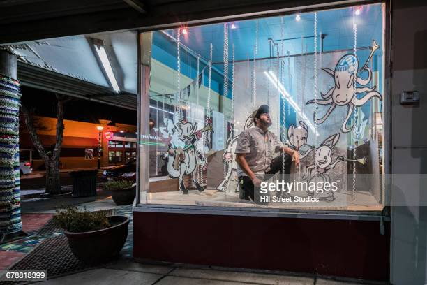 Hispanic man decorating display window in music store