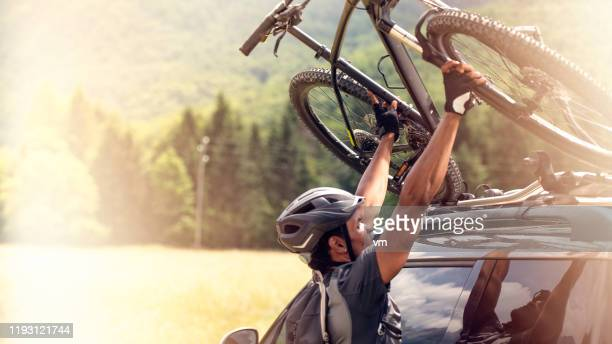 hispanic man dismounting his mountain bike from a car roof rack - cross country cycling stock pictures, royalty-free photos & images