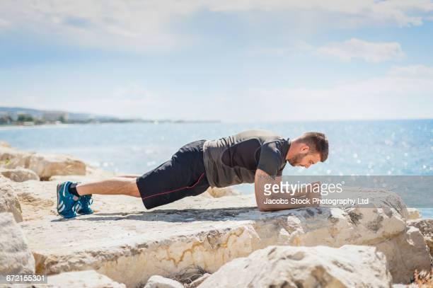 Hispanic man doing push-ups on rock near ocean