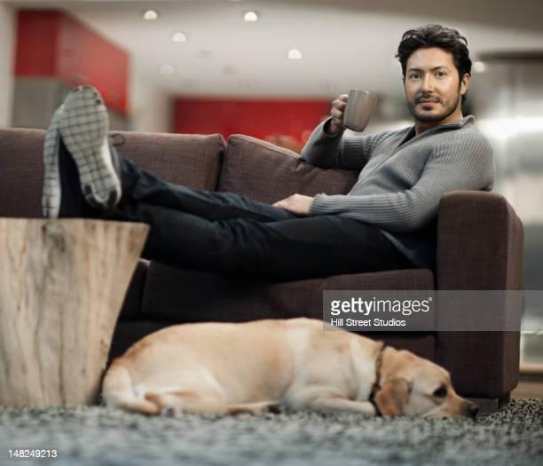 Hispanic Mann, trinkt Kaffee auf sofa mit Hund in der Nähe