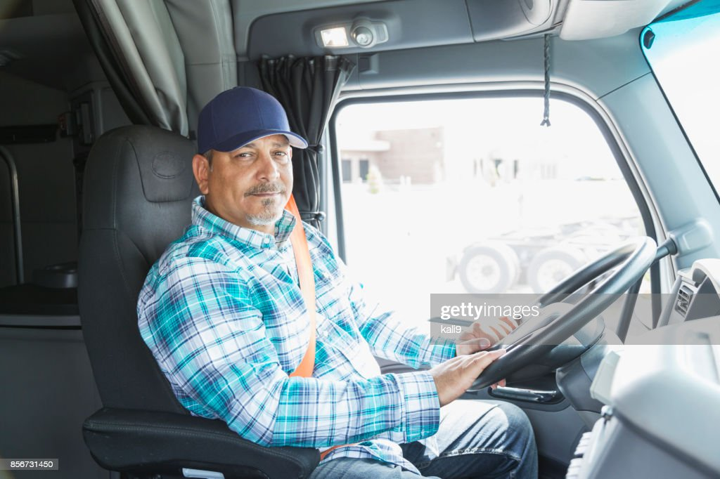 Hispanic man driving a semi-truck : Stock Photo