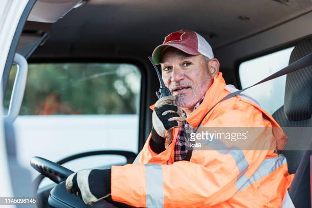 hispanic man driving a truck - driver occupation stock pictures, royalty-free photos & images