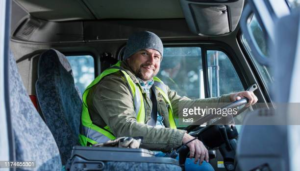hispanic man driving a truck - reflective clothing stock pictures, royalty-free photos & images