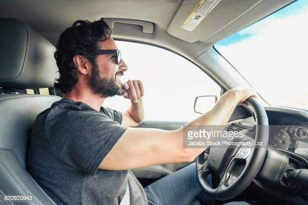 Hispanic man driving car