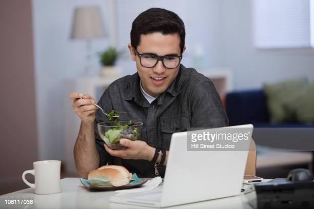 Hispanic Mann Essen Mittagessen und arbeiten auf laptop