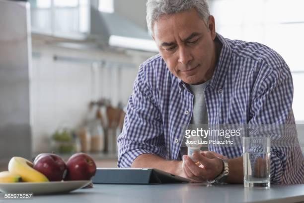 hispanic man examining prescription bottle in kitchen - prescription medicine stock pictures, royalty-free photos & images