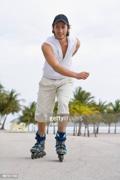 Hispanic man exercising on rollerblades
