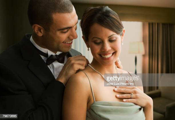 Hispanic man fastening wife's necklace