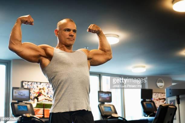 Hispanic man flexing biceps gymnasium