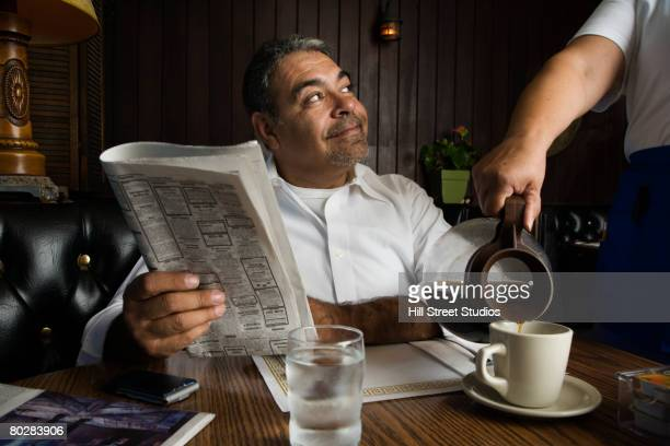 hispanic man getting coffee at diner - diner stock pictures, royalty-free photos & images
