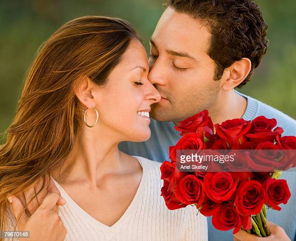Hispanic man giving flowers to wife