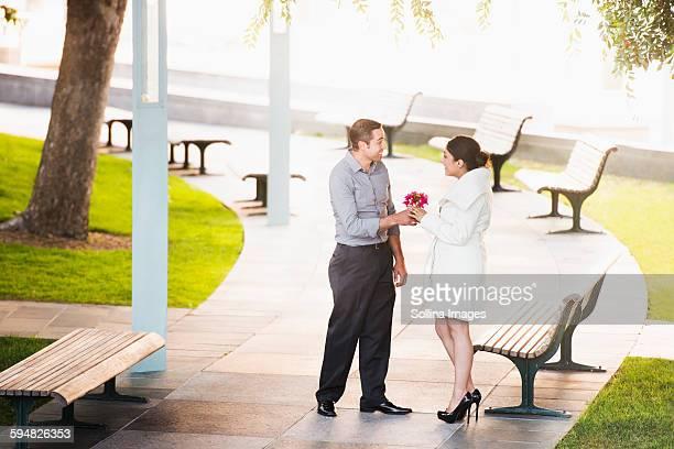 Hispanic man giving girlfriend flowers in park