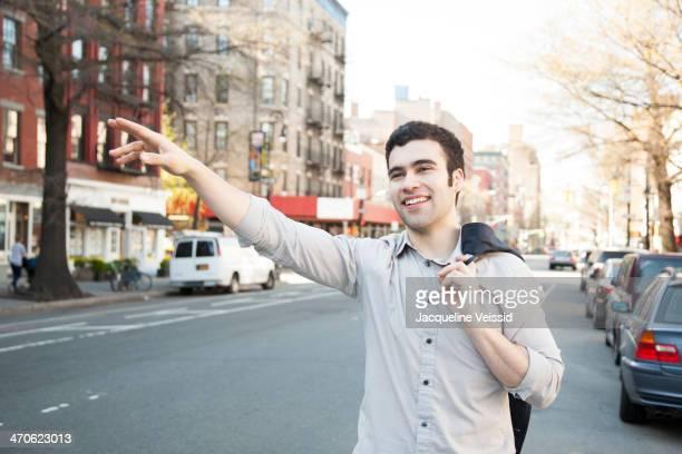 Hispanic man hailing taxi on city street