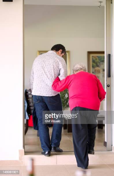 Hispanic man helping his grandmother to walk