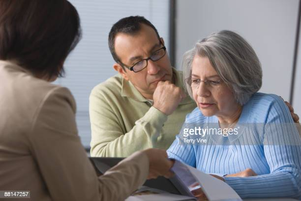 Hispanic man helping mother read sales contract