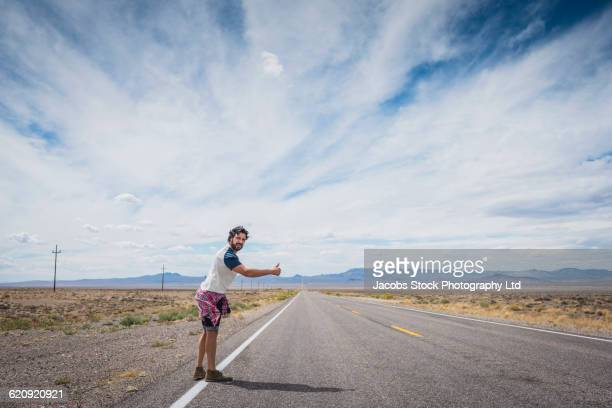 hispanic man hitchhiking on remote road - hitchhiking stock pictures, royalty-free photos & images