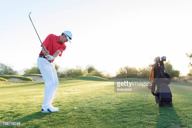 Hispanic man hitting ball on golf course