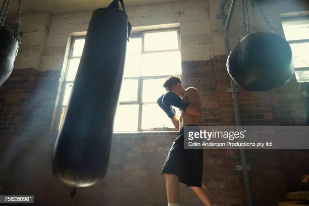 Hispanic man hitting punching bag in gymnasium