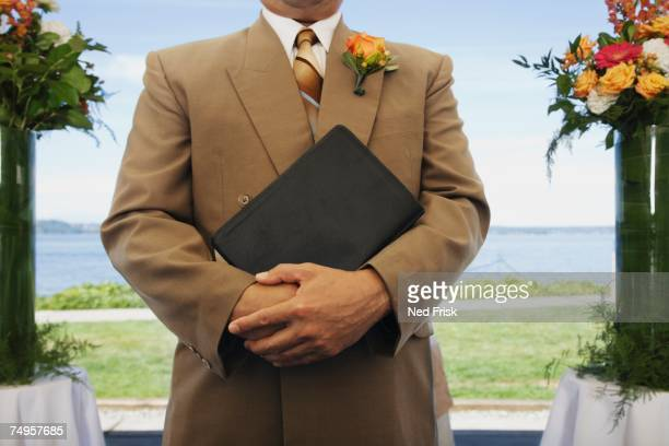 hispanic man holding book - pastor stock pictures, royalty-free photos & images
