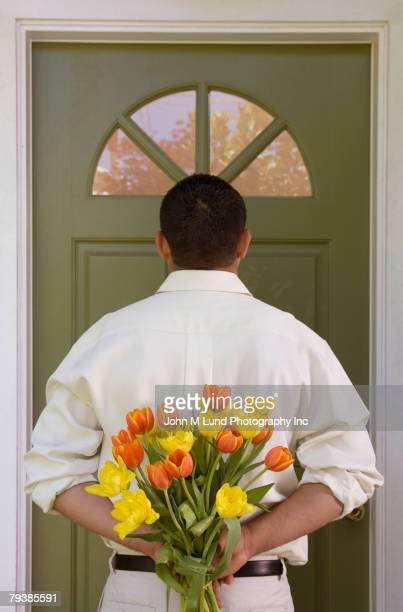 Hispanic man holding flowers behind back