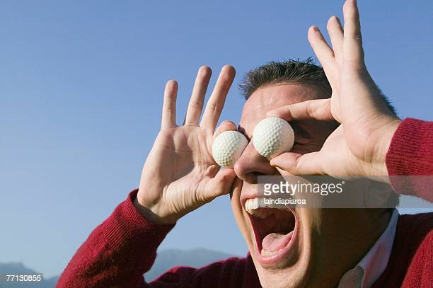 hispanic man holding golf balls over eyes - golf humour photos et images de collection