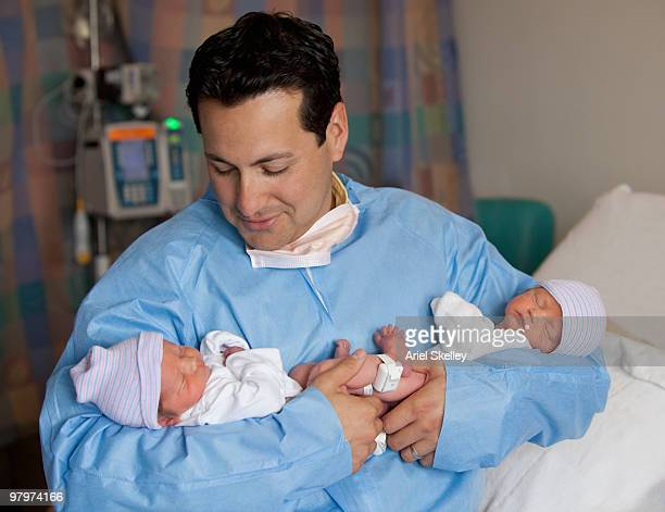 hispanic man holding newborn babies - twin stock pictures, royalty-free photos & images