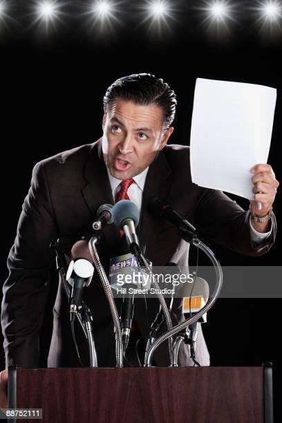 Hispanic man holding paper at press conference podium