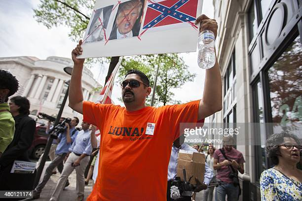 Hispanic man holds a sign while marching to Trump Hotel during a protest against Donald Trump, candidate for the Republican Presidential ticket,...